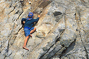 Barefoot boy climbing on rock at Sand Dollar Beach on the Big Sur Coast, Los Padres National Forest, California