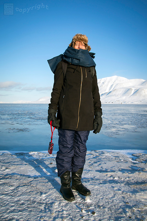 One woman standing on waters edge in freezing climate with camera