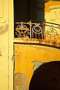 Rusting wrought iron balcony, peeling paint, crumbling masonry. Opatija, Croatia