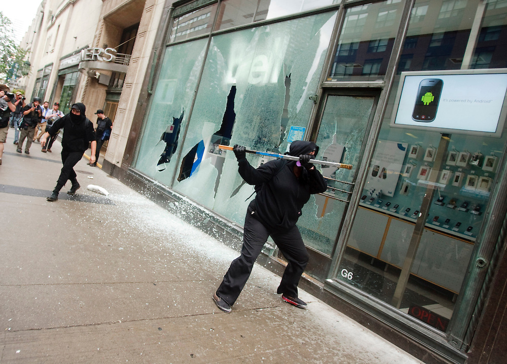 Protesters smash windows in the Toronto's downtown core June 26, 2010 after a small group of anarchists broke from the main anti G20 demonstration and began a destructive march through the downtown.<br /> AFP/GEOFF ROBINS/STR