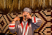 An Ainu woman plays a traditional stringed instrument - the Mukkur.