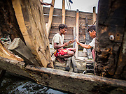 07 NOVEMBER 2014 - SITTWE, RAKHINE, MYANMAR: Rohingya Muslim workers make a new boat near the port of an IDP camp for Rohingya Muslims near Sittwe. The government of Myanmar has forced more than 140,000 Rohingya Muslims who used to live in Sittwe, Myanmar, into squalid Internal Displaced Person (IDP) camps. The forced relocation took place in 2012 after sectarian violence devastated Rohingya communities in Sittwe and left hundreds dead. None of the camps have electricity and some have been denied access to regular rations for nine months. Conditions for the Rohingya in the camps have fueled an exodus of Rohingya refugees to Malaysia and Thailand. Tens of thousands have put to sea in rickety boats hoping to land in Malaysia but sometimes landing in Thailand. The exodus has fueled the boat building boom on the waterfront near the camps. Authorities expect the pace of refugees fleeing Myanmar to accelerate during the cool season, December through February, when there are fewer storms in the Andaman Sea and Bay of Bengal.   PHOTO BY JACK KURTZ