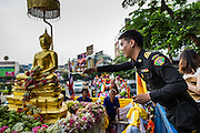 12 APRIL 2014 - BANGKOK, THAILAND:  People bathe the Phra Buddha Sihing statue with scented oils. The Phra Buddha Sihing, a revered statue of the Buddha, is carried by truck through the streets of Bangkok so people can make offerings and bathe it in scented oils. Songkran is celebrated in Thailand as the traditional New Year's from 13 to 16 April. The date of the festival was originally set by astrological calculation, but it is now fixed. The traditional Thai New Year has been a national holiday since 1940, when Thailand moved the first day of the year to January 1. The first day of the holiday period is generally the most devout and many people go to temples to make merit and offer prayers for the new year.    PHOTO BY JACK KURTZ