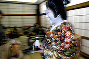 Geisha Norie carries in drinks for customers at a geisha house in Tokyo, Japan.