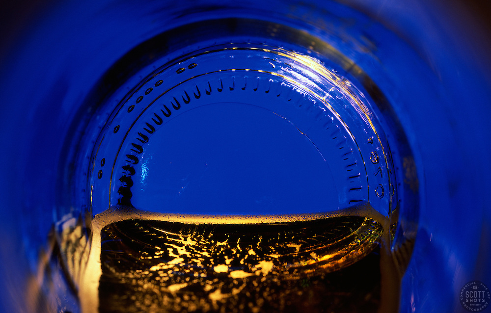 """""""Beauty at the Bottom: Blue""""- This image is a photograph of a beer bottle shot right down the mouth of the bottle. A television provides the main light source."""