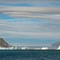 Low clouds sweep over icebergs in Dygalski Fjord on South Georgia Island.