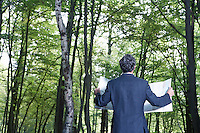 Mid adult man in suit jacket standing in forest with map back view
