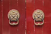 Traditional Chinese vermillion door with brass lion knockers in Beijing, China