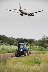 CAPTION CORRECTION - AIRCRAFT IS NOT A BOEING 747 © Licensed to London News Pictures. 05/06/2018. London, UK. A passenger jet comes into land at Heathrow airport near a tractor ploughing a field. The government has announced a third runway will go ahead at Heathrow. Photo credit: Peter Macdiarmid/LNP