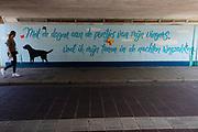 In Eindhoven passeert een vrouw een muurschildering met de tekst 'Met de dagen aan de puntjes van mijn vingers voel ik mijn tenen in de nachten wegzakken' in de tunnel.<br /> <br /> Om Eindhoven a woman passes a wall painting in a tunnel/