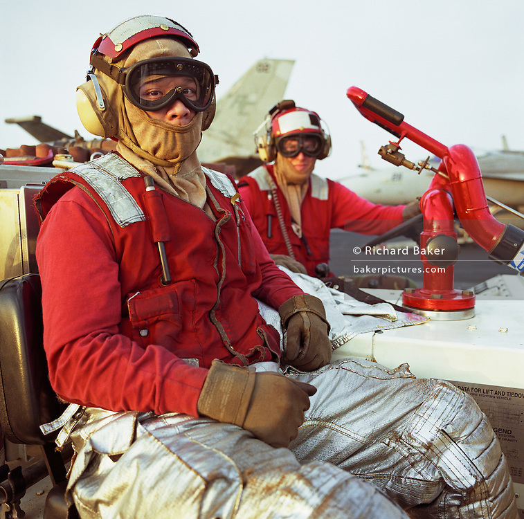 "Two crewmen aboard the US Navy aircraft carrier USS Harry S Truman sit on a fire vehicle on the ship's deck. Wearing red signifies that they are part of a crash and salvage team who respond to emergencies and fire hazards and so wear flame-retardant and anti-flash clothing material. Ordinarily they are responsible for making safe and towing (""doing the bow dance"") $38 million F/A-18s fighters round the deck of the Navy?s newest aircraft carrier, here on coalition patrol somewhere off Kuwait in the Arabian Sea. The Truman is so called after the US President who was in office from 1945 to 1953.  Picture from the 'Plane Pictures' project, a celebration of aviation aesthetics and flying culture, 100 years after the Wright brothers first 12 seconds/120 feet powered flight at Kitty Hawk,1903."