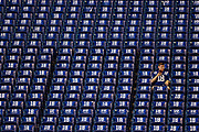 A fan watches while sitting amongst commemorative towels on the stadium seats as the San Francisco 49ers and the Indianapolis Colts warm up for an NFL football game, Sunday, Oct. 8, 2017, in Indianapolis.
