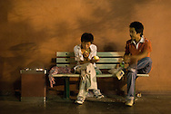 Two teenagers spending the night on a bench. During summer nights, on Changan jie, near Tian An Men square, the benches are occupied by tourists, homeless, migrant-workers who spend the night there waiting for the sun to rise.
