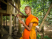 """02 JULY 2013 - ANGKOR WAT, SIEM REAP, SIEM REAP, CAMBODIA:  A Buddhist monk in his monastery near the Bayon temple in the Angkor Wat complex.  Angkor Wat is the largest temple complex in the world. The temple was built by the Khmer King Suryavarman II in the early 12th century in Yasodharapura (present-day Angkor), the capital of the Khmer Empire, as his state temple and eventual mausoleum. Angkor Wat was dedicated to Vishnu. It is the best-preserved temple at the site, and has remained a religious centre since its foundation– first Hindu, then Buddhist. The temple is at the top of the high classical style of Khmer architecture. It is a symbol of Cambodia, appearing on the national flag, and it is the country's prime attraction for visitors. The temple is admired for the architecture, the extensive bas-reliefs, and for the numerous devatas adorning its walls. The modern name, Angkor Wat, means """"Temple City"""" or """"City of Temples"""" in Khmer; Angkor, meaning """"city"""" or """"capital city"""", is a vernacular form of the word nokor, which comes from the Sanskrit word nagara. Wat is the Khmer word for """"temple grounds"""", derived from the Pali word """"vatta."""" Prior to this time the temple was known as Preah Pisnulok, after the posthumous title of its founder. It is also the name of complex of temples, which includes Bayon and Preah Khan, in the vicinity. It is by far the most visited tourist attraction in Cambodia. More than half of all tourists to Cambodia visit Angkor.         PHOTO BY JACK KURTZ"""