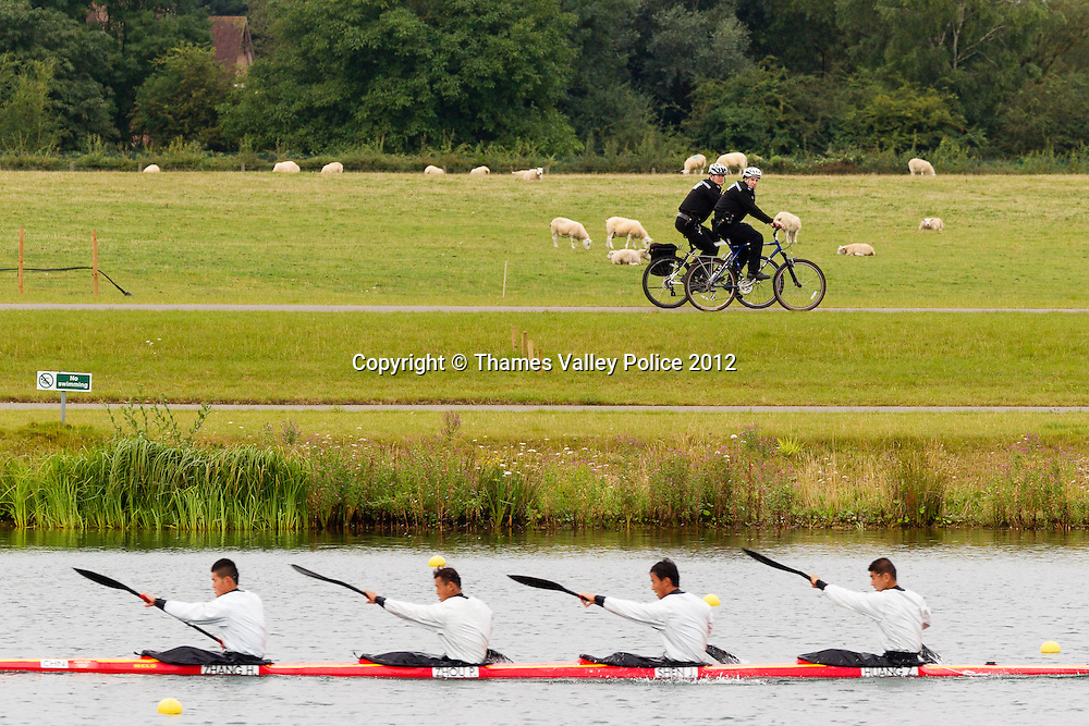 Two cycle mounted officers from Thames Valley Police patrol the lakeside at the Eton Dorney Olympic Venue during the London 2012 Games as the Chinese team prepare for their heat in the K4 1000m. Eton Dorney, UNITED KINGDOM. August 07 2012. <br /> Photo Credit: MDOC/Thames Valley Police<br /> &copy; Thames Valley Police 2012. All Rights Reserved. See instructions.