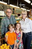 Portrait of happy children with grandparents in produce market