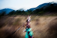 A Samburu warrior throws his spear at dusk in Matthews Range, Kenya.