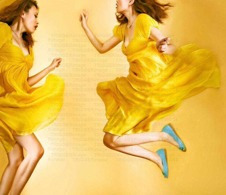 Young asian female wearing yellow dress dancing and jumping
