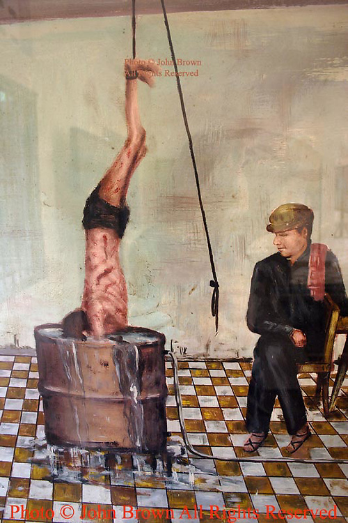 A painting by Vann Nath, a prisoner himself, depicts Pol Pot's Khmer Rouge regime prison guards torturing an inmate at The Tuol Sleng Genocide Museum in Phnom Penh Cambodia.