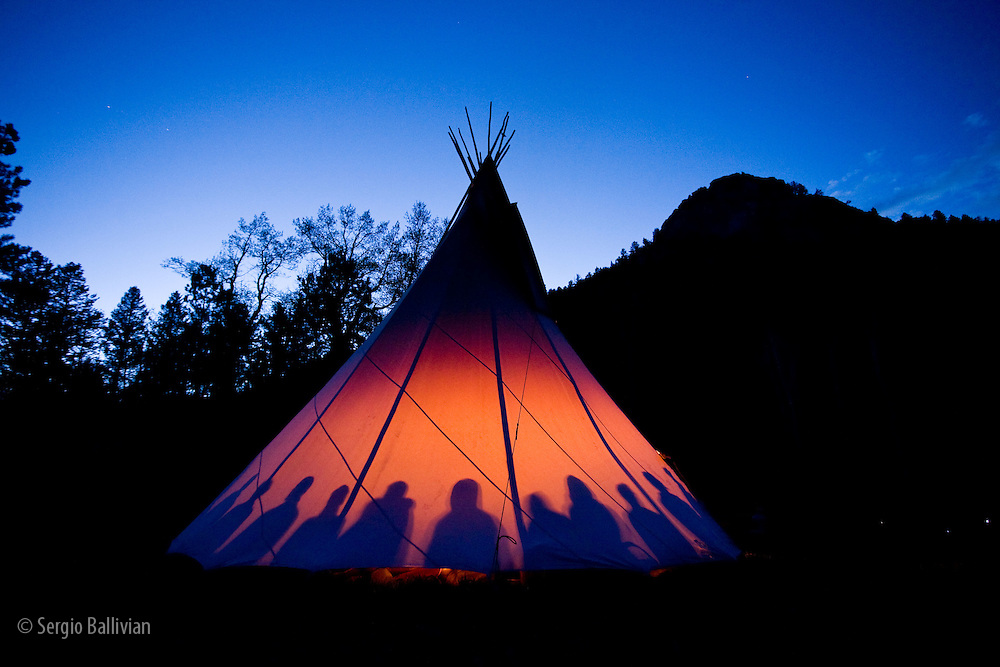 A fire creates a glow from inside a teepee at dusk as people gather for a ceremony in Boulder, Colorado.