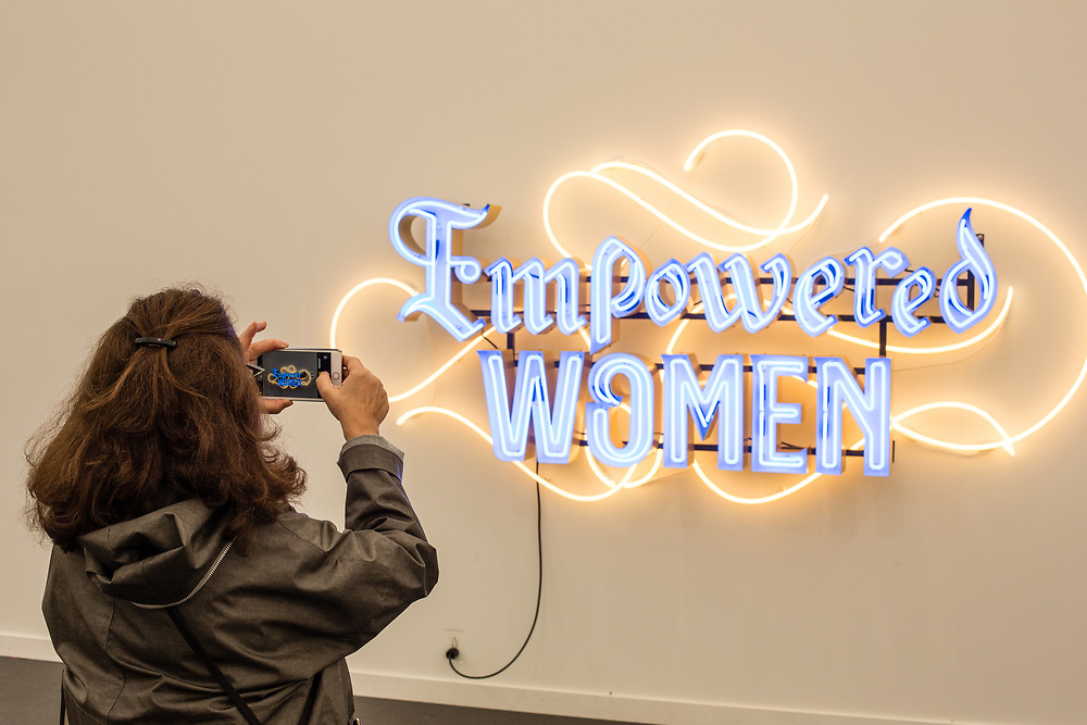 "New York, NY - May 3, 2019. A woman takes a photo of a neon scupture that reads ""Empowered Women"" at the Frieze Art Fair on New York City's Randalls Island."