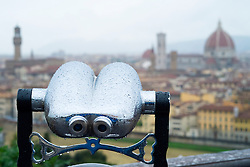 View of skyline of Florence in Italy  with public viewing binoculars in foreground