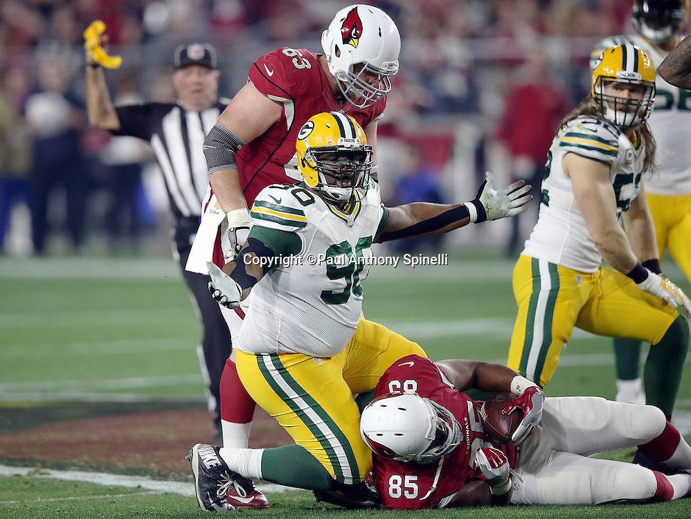 Arizona Cardinals tight end Darren Fells (85) lies on the ground while Green Bay Packers nose tackle B.J. Raji (90) waves his arms and complains about an unnecessary roughness penalty that gives the Cardinals a first down during the NFL NFC Divisional round playoff football game against the Green Bay Packers on Saturday, Jan. 16, 2016 in Glendale, Ariz. The Cardinals won the game in overtime 26-20. (©Paul Anthony Spinelli)