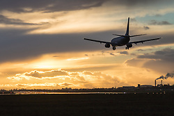 Heathrow Airport, London, March 28th 2016. A Boeing 737 is silhouetted against clouds illuminated by the setting sun, about to land at London Heathrow.
