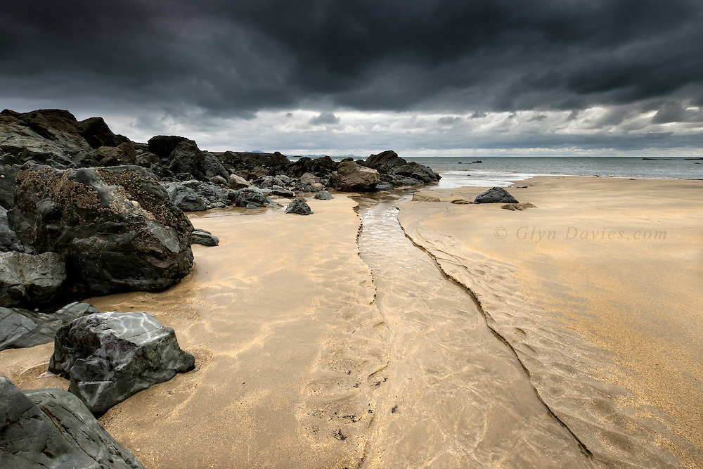 A stream cuts down the beach to reach the door, carving beautiful curves through virgin sand. Black clouds stall overhead and light levels dropped dramatically, yet, there was a sombre beauty in this endlessly fascinating stretch of coast, regardless of weather.