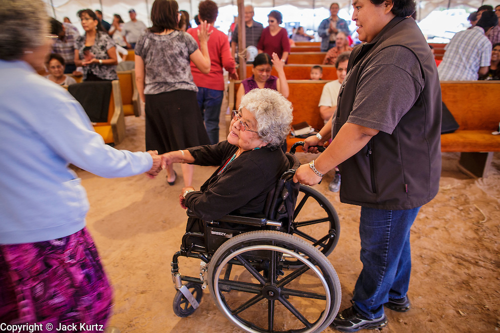 "12 JULY 2012 - FT DEFIANCE, AZ:  Sister ANGIE BOWMAN greets people at the 23rd annual Navajo Nation Camp Meeting in Ft. Defiance, north of Window Rock, AZ, on the Navajo reservation, Thursday night. Bowman has been coordinating the camp meeting since its founding 23 years ago. Preachers from across the Navajo Nation, and the western US, come to Navajo Nation Camp Meeting to preach an evangelical form of Christianity. Evangelical Christians make up a growing part of the reservation - there are now more than a hundred camp meetings and tent revivals on the reservation every year. The camp meeting in Ft. Defiance draws nearly 200 people each night of its six day run. Many of the attendees convert to evangelical Christianity from traditional Navajo beliefs, Catholicism or Mormonism. ""Camp meetings"" are a form of Protestant Christian religious services originating in Britain and once common in rural parts of the United States. People would travel a great distance to a particular site to camp out, listen to itinerant preachers, and pray. This suited the rural life, before cars and highways were common, because rural areas often lacked traditional churches. PHOTO BY JACK KURTZ"