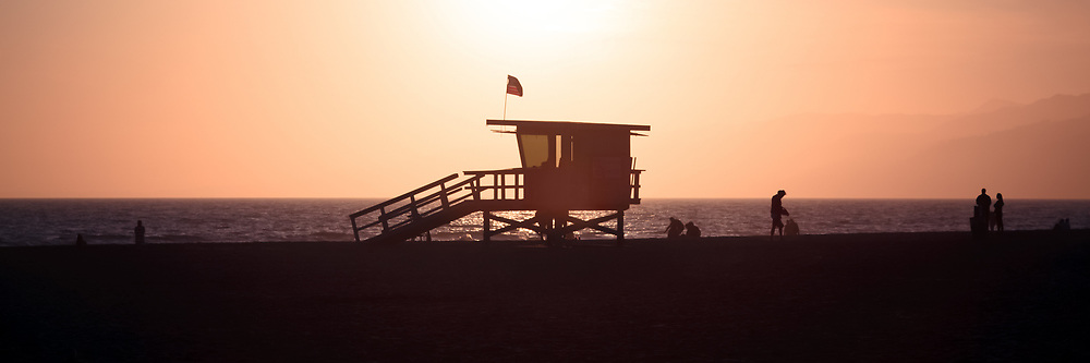 Santa Monica lifeguard tower panorama photo at sunset. Picture was taken in 2012 at Santa Monica State Beach Park in Los Angeles County Southern California. Panoramic photo ratio is 1:3 and has a vintage nostalgic tone.
