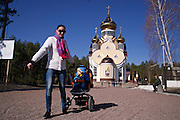 A woman with a pram outside the new Orthodox church in the town of Slavutych, which has some of the highest birth rates in Ukraine. <br /> <br /> Slavutych rises out of the ashes of the Chernobyl nuclear disaster in April 26, 1986. People living near the disaster area were largely moved to the new city, built from scratch for the sole purpose of housing the population displaced by the nuclear accident.