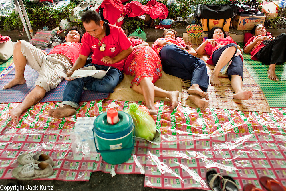 "18 APRIL 2010 -- BANGKOK, THAILAND: Most of the Red Shirts pass the days sleeping in the shade created by the Bangkok ""Skytrains"" during the protests in the shopping district. The Red Shirts protest in the Ratchaprasong Shopping district, home to Bangkok's most upscale malls, is costing the Thai economy millions of Baht per day because the malls and most of the restaurants are closed and tourists are staying away from the area. But that hasn't stopped the Red Shirts who have brought their own economy with them. There are Red Shirt restaurants, food stands, souvenir vendors and more, creating a micro economy for Red Shirts in the area.  The Red Shirts continue to occupy Ratchaprasong Intersection an the high end shopping district of Bangkok. They are calling for Thai Prime Minister Abhisit Vejjajiva to step down and dissolve the parliament. Most of the Red Shirts support ousted former Prime Minister Thaksin Shinawatra.   PHOTO BY JACK KURTZ"