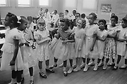 School integration. Barnard School, Washington, D.C. Line of African American and white schoolgirls standing in a classroom while boys sit behind them:  27 May 1955. Photographer: Thomas J O'Halloran.