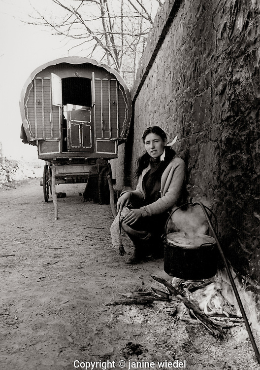 Irish Traveller woman cooking in front of her traditional bow caravan in Southern Ireland  1970's.