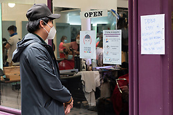 © Licensed to London News Pictures. 04/07/2020. London, UK. A customer queues outside a barbers for a haircut in Chinatown after a relaxing of rules during the Covid-19 pandemic. Photo credit: Ray Tang/LNP.