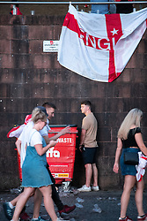 © Licensed to London News Pictures . 11/07/2018. Manchester, UK. Fans disperse after the match . One urinates against a wheelie bin . Football fans watch England play against Croatia in the World Cup semi finals, on a big screen at Castlefield Bowl in Manchester City Centre . Until today , Manchester had been the largest city in England not to be showing World Cup matches to the public on a big screen . Photo credit: Joel Goodman/LNP