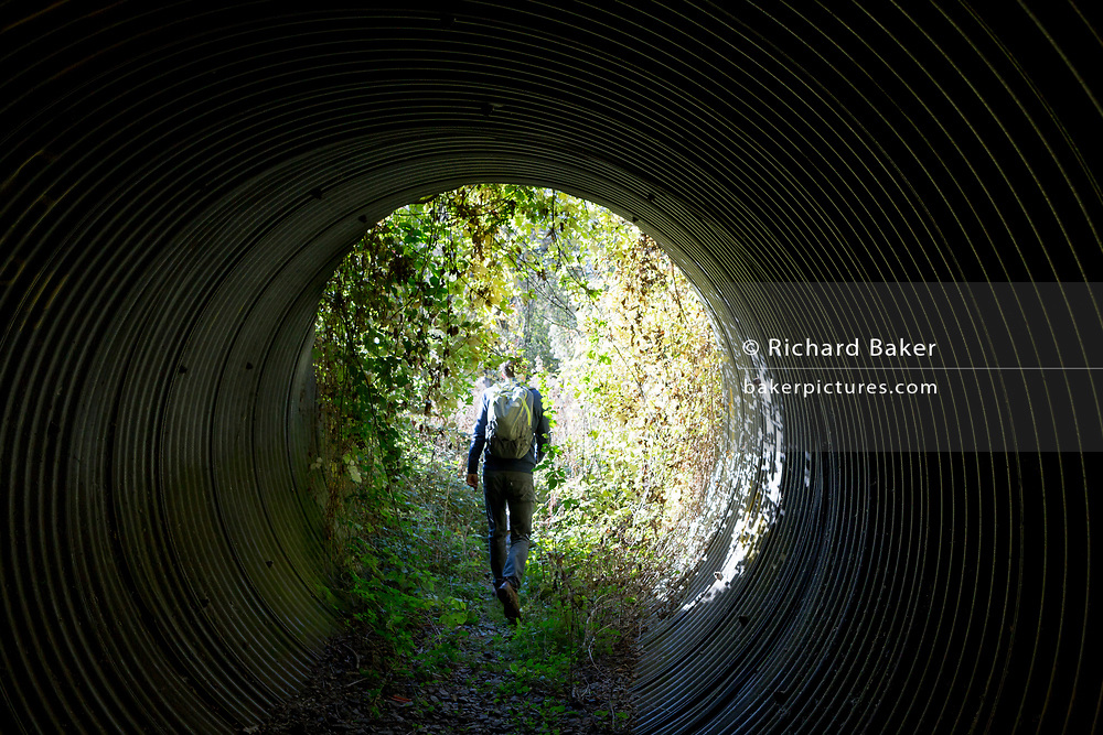 A country walker emerges from a dark foot tunnel under a railway line, into bright sunlight, on 21st October 2018, near Hollingbourne;, Kent, England.