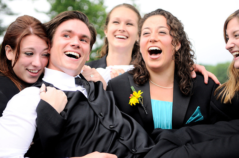 Bridesmaids embrace and lift the groom  on the lawn of Sleepy Hollow Country Club.