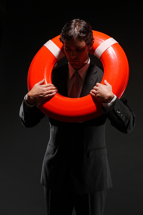 Businessman poses with life preserver - illustration of business bailout (D.Mciver model)