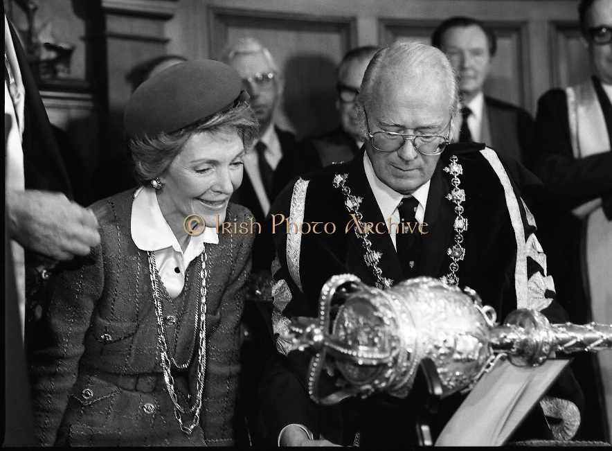 Nancy Reagan .Visits the Royal College Of Surgeons..St Stephens Green,.1984..04.06.1984.06.04.1984.4th June 1984..Nancy Reagan visited the Royal College of Surgeons where she unveilled a portrait of her late father.Her father, Dr Loyal Davis was an Honorary Fellow of the college. Mrs Reagan then presented the portrait to the college..Under the shadow of the college mace Professor O'Malley signs the commerative book for Mrs Nancy Reagan..Image of Mrs Nancy Reagan as she is distracted by something happening on her right.