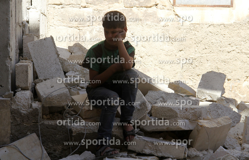 06.07.2015, Aleppo, SYR, B&uuml;rgerkrieg in Syrien, im Bild ein junger Syrer nachdenklich in der zerst&ouml;rten Stadt // A Syrian boy looks on as he sits on the ruins of a destroyed building following a reported bomb barrel attack by Syrian government forces hit al-Mayser rebel held neighborhood, Syria on 2015/07/06. EXPA Pictures &copy; 2015, PhotoCredit: EXPA/ APAimages/ Ameer al-Halbi<br /> <br /> *****ATTENTION - for AUT, GER, SUI, ITA, POL, CRO, SRB only*****