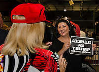 "Mary Ann Logsdon of Laconia shows off her ""Deplorables for Trump"" sign to Ruthie Reingold at Laconia Middle School Thursday evening.  (Karen Bobotas/for the Laconia Daily Sun)"