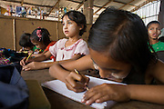 "25 FEBRUARY 2008 -- MAE SOT, TAK, THAILAND: The children of Burmese migrants take classes at the Blue Sky School near the garbage dump in Mae Sot, Thailand. The students at the school are all the children of Burmese migrants who work in the garbage dump, sorting and selling what they find amid the trash. There are millions of Burmese migrant workers and refugees living in Thailand. Many live in refugee camps along the Thai-Burma (Myanmar) border, but most live in Thailand as illegal immigrants. They don't have papers and can not live, work or travel in Thailand but they do so ""under the radar"" by either avoiding Thai officials or paying bribes to stay in the country. Most have fled political persecution in Burma but many are simply in search of a better life and greater economic opportunity.  Photo by Jack Kurtz"