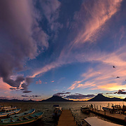 Sunset lights up the sky over Lake Atitlan, Guatemala, from the dock at Santa Cruz la Laguna.