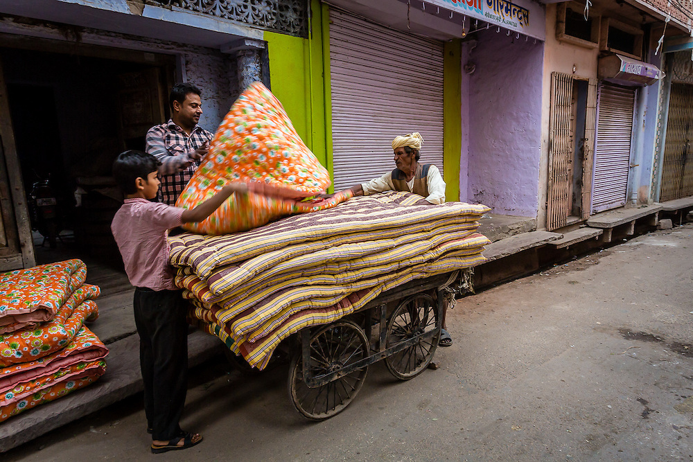 Early morning in Bundi. A man and his son are loading a cart with old mattresses so that the seller can take them away.