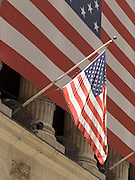 detail of the very large American flag draped over the pillars of the NY Stock Exchange