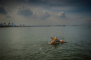 "Man on a ""kayak"" made by recovered bamboo and styrofoam paddles out into Manila Bay to go fishing because he cannot afford a fishing boat.  Manila Bay, off of Baseco slum, Manila, Philippine."