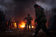 A refugee boy pushes a bicycle away from a fire in the Calais refugee camp known as the 'jungle' in January 2016.