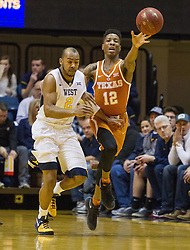 Feb 20, 2017; Morgantown, WV, USA; Texas Longhorns guard Kerwin Roach Jr. (12) passes the ball while guarded by West Virginia Mountaineers guard Jevon Carter (2) during the first half at WVU Coliseum. Mandatory Credit: Ben Queen-USA TODAY Sports